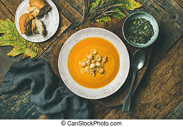 Warming pumpkin cream soup with croutons and seeds in plate
