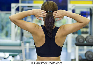 Warming Up - A female fitness instructor stretches with her...
