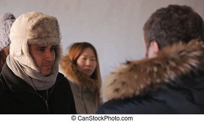 Warmly dressed tourists listen to a man-guide, who tells...