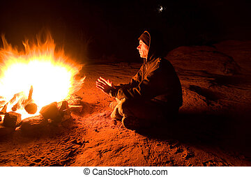 Warmth - Man warming himself in front of fire on a cold...
