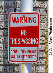 Warning No Trespassing sign against a metal pole and rough brick wall