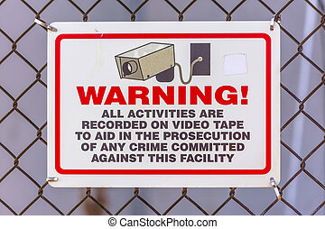 Warning security camera sign on a chain link fence