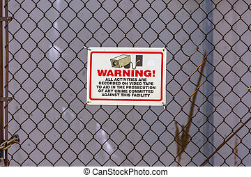 Warning security camera sign on chain link fence