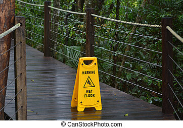Warning sign for slippery floor on a wooden path of a rain forest
