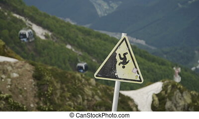 Warning sign on the top of mountain. Cable car with cabins -...