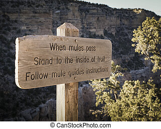 Warning sign regarding mules pass on trail