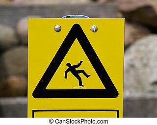 Warning sign slippery floor surface outdoors on a wooden...