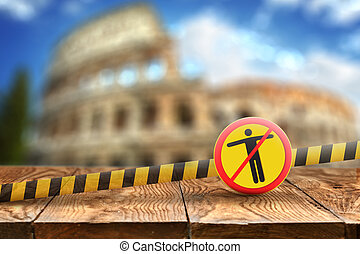 Warning sign with crossed out man on the background of wooden table and blurred Colosseum in Rome, Italy.