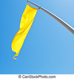 warning sign - yellow flag with blue sky