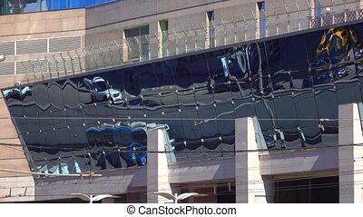 Warped street traffic reflections in mirror facade of modern...