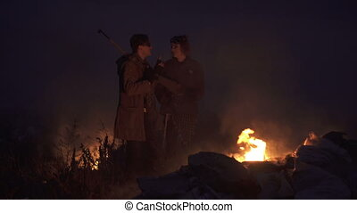 Warrior girl and Stalker survivor Soldier in an Apocalypse War scenario stay near the smoke of fire with rifle