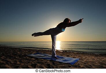 Warrior III yoga pose on beach