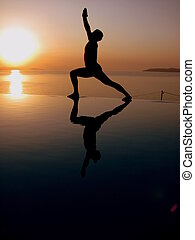 A Man in Warrior pose at the beach