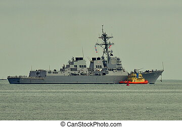 Warship guided by a Harbor Tug.