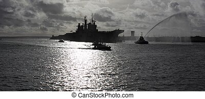 PORTSMOUTH, ENGLAND, 10TH JANUARY 2014 HMS Illustrious, the aircraft carrier returns to portsmouth after its deployment to the Philippines with a water canon salute from the tugboats