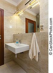 Wash basin in modern bathroom with travertine tiles
