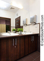 Wash basin in wooden counter in public bathroom