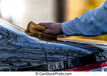 Wash car - Hand with yellow sponge wash of a black car