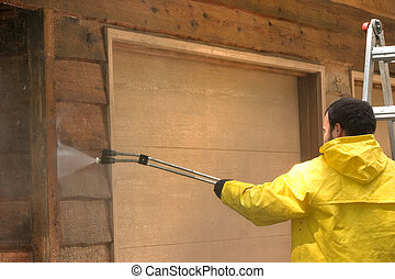 Wash It Down - a man pressure washing a wood sided garage