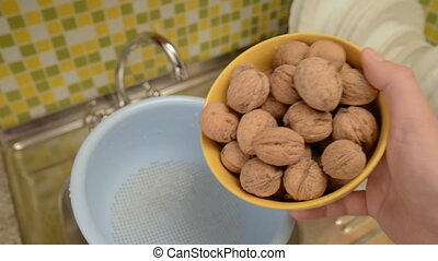 Wash the nuts in the colander in the kitchen.