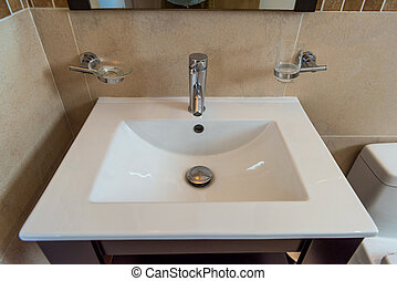 Washbasin in the bathroom, beige with chrome accessories. Modern repair.