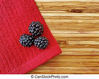Washed blackberries on a red cloth in kitchen.