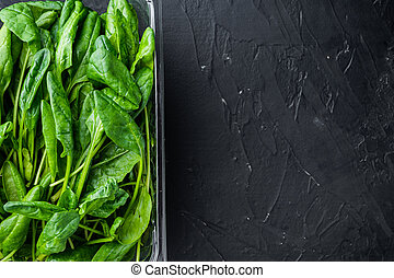 Washed fresh mini spinach, on black background, in plastic pack, top view flat lay , with space for text copyspace