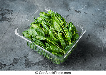 Washed fresh mini spinach, on gray background, in plastic pack