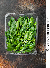 Washed fresh mini spinach, on old dark rustic background, in plastic pack, top view flat lay