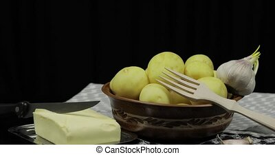 Washed fresh potatoes on table ready for cooking. Butter,...