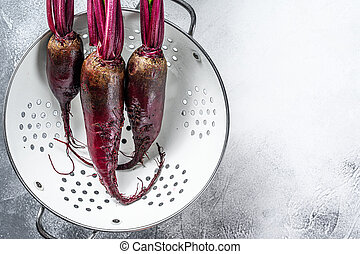 Washed organic purple beetroot in a colander. Gray background. Top view. Copy space