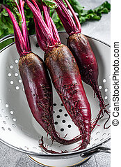 Washed organic purple beetroot in a colander. Gray background. Top view
