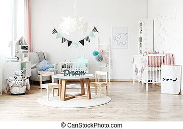 Washi tape hanging over a child's white cradle standing next to a large armchair with a cloud shaped blue blushing pillow looking in the direction of wooden chest of drawers filled with accessories