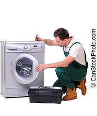 Washing - A repairman holding a spanner and posing next to a...