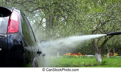 washing automobile car with strong water jet in garden.