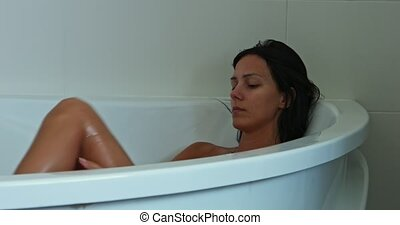 Washing body in bath - Young brunette woman taking bath with...