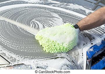Washing car - A man uses a soft, green micro fiber mitt mied...