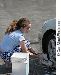Washing Car Tires - A teenaged girl washing car tires with a...