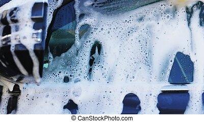 Washing car with sponge and shampoo, hand spreading foam on ...