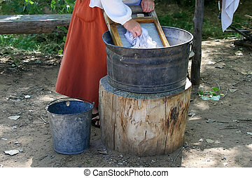 Washing Clothes on a Washboard - A woman in a long red skirt...