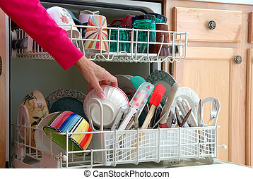 Washing Dishes - A female hand is shown loading dishes into the dishwasher.