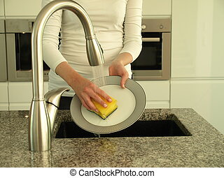 Washing dishes - Woman's hands washing plate with sponge and...
