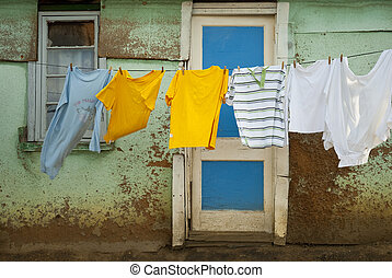 Washing drying in front of shack - Cyan and yellow and white...