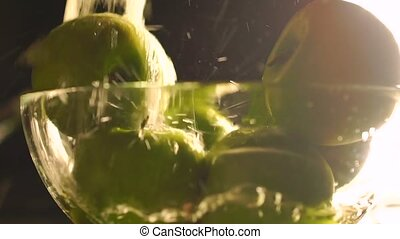 Washing green apples in a glass bowl, slow motion video