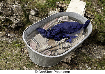 Washing handwoven carpets in a metal tub over a small creek