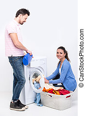 Washing - Housework. Young woman and man are doing laundry ...