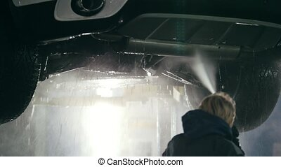 Washing luxury SUV under bottom in the suds by water hoses -...