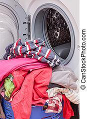 Washing machine - Open washing machine and pile of clothes