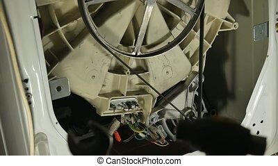 Washing machine repair, rear view. Multimeter check. - Man...
