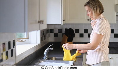 Washing Plates - Middle Age Woman Washing Dishes At The...